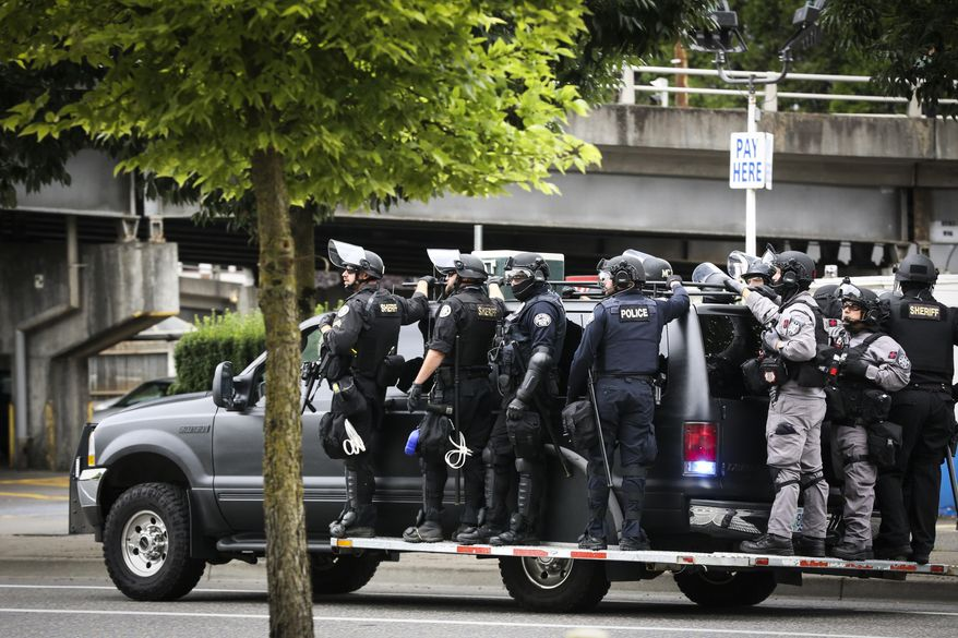 Portland Police prepare to head towards Tom McCall Waterfront Park as right-wing groups and counterprotesters gathered in downtown Portland, Ore., on Saturday, Aug. 17, 2019.  Flag-waving members of the Proud Boys and Three Percenters militia group began gathering late in the morning, some wearing body armor and helmets. Meanwhile black clad, helmet and mask-wearing anti-fascist protesters  known as antifa  were also among the several hundred people on the streets. (AP Photo/Moriah Ratner)