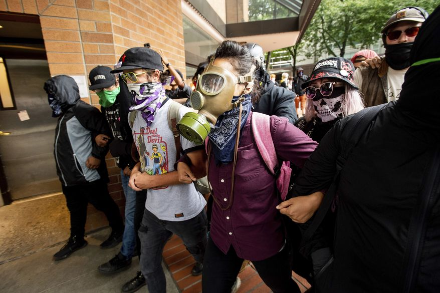 "Protesters gathered to oppose right-wing demonstrators face off against police following an ""End Domestic Terrorism"" rally in Portland, Ore., on Saturday, Aug. 17, 2019. Although the main protest remained largely peaceful, some skirmishes erupted in the following hours and police detained multiple protesters. (AP Photo/Noah Berger)"