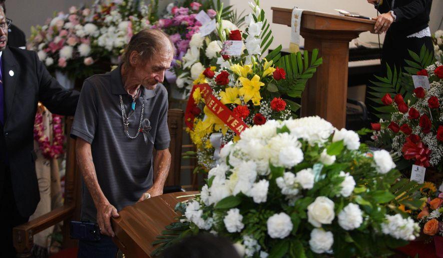 Antonio Basco, companion of Margie Reckard, leans on her casket during her funeral at La Paz Faith Memorial & Spiritual Center, Friday, Aug. 16, 2019, in El Paso, Texas. Reckard was killed during the mass shooting on Aug. 3. (AP Photo/Jorge Salgado)