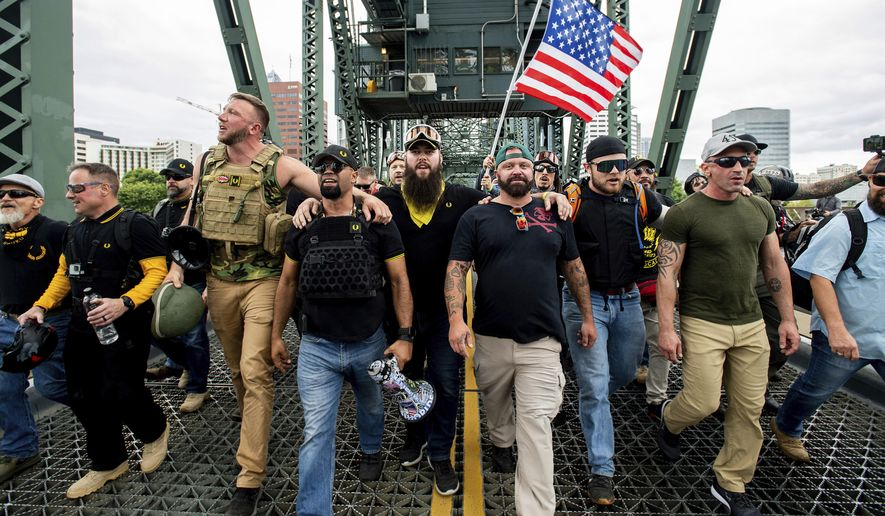 "Members of the Proud Boys and other right-wing demonstrators march across the Hawthorne Bridge during an ""End Domestic Terrorism"" rally in Portland, Ore., on Saturday, Aug. 17, 2019. The group includes organizer Joe Biggs, in a green hat, and Proud Boys Chairman Enrique Tarrio, holding megaphone. (AP Photo/Noah Berger) ** FILE **"