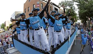 The Caribbean Region Champion Little League team from Willemstad, Curacao, rides in the Little League Grand Slam Parade in downtown Williamsport, Pa., Wednesday, Aug. 14, 2019. The Little League World Series baseball tournament, featuring 16 teams from around the world, starts August 15, 2019 in South Williamsport, Pa. (AP Photo/Gene J. Puskar)