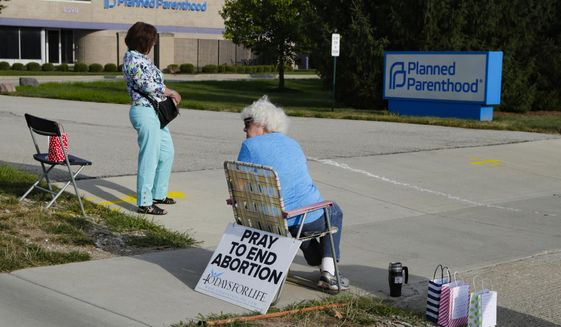 Abortion protesters stand in the driveway of a Planned Parenthood clinic in Indianapolis, Friday, Aug. 16, 2019. Planned Parenthood of Indiana and Kentucky is receiving a nearly $1 million funding boost and is adding staffers under its merger with the group's Seattle-based affiliate. (AP Photo/Michael Conroy)