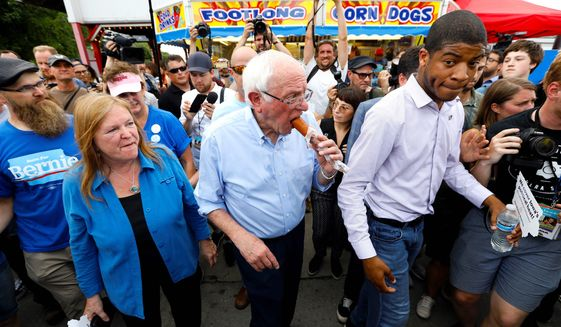 Presidential candidate Sen. Bernard Sanders eats a corn dog with his wife, Jane, (left) at Iowa State Fair in Des Moines, Iowa. (ASSOCIATED PRESS)