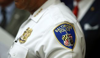 In this Aug. 29, 2018 file photo, a patch depicting the Baltimore Police Department seal is seen on Interim Commissioner Gary Tuggle's uniform as he speaks at a news conference in Baltimore. The city has been casting for its fourth police leader in a year while the flailing department faces pressure to bring down violent crime levels that are among the nation's worst. (AP Photo/Patrick Semansky, File)
