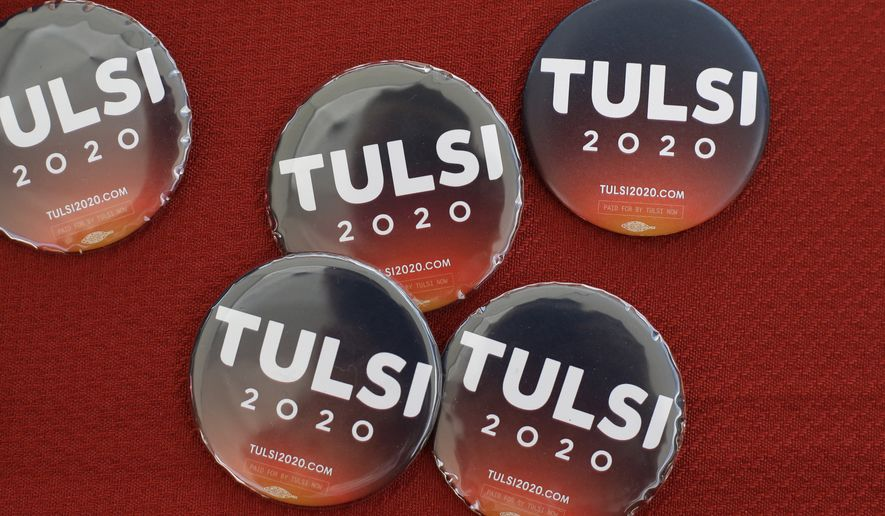 Buttons for Democratic presidential candidate Rep. Tulsi Gabbard rest on a table, Sunday, Aug. 18, 2019, at the Hillsborough County Democrats Summer Picnic, in Greenfield, N.H. (AP Photo/Steven Senne)