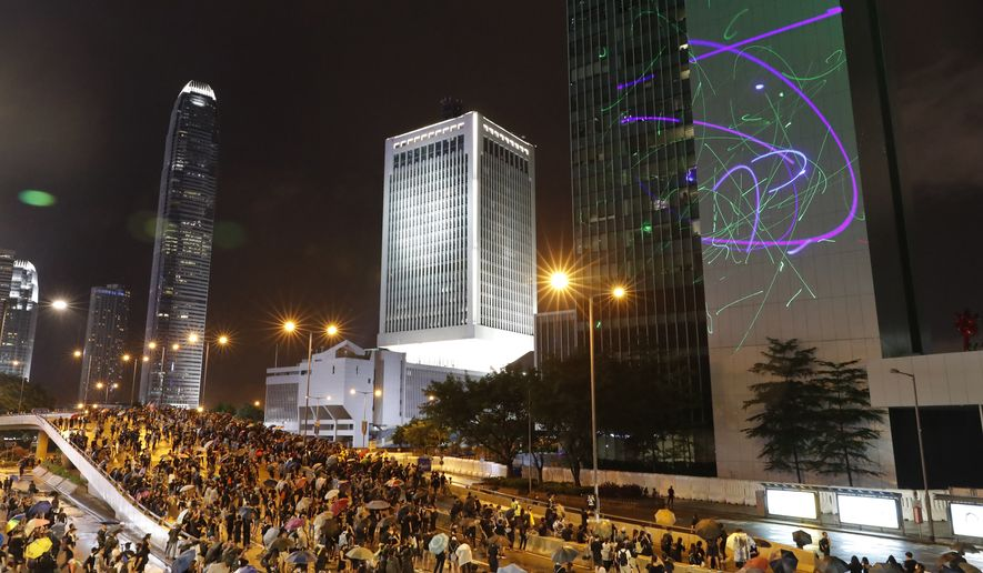 Protesters shine laser pointers on the Government Headquarters complex in Hong Kong, Sunday, Aug. 18, 2019. Heavy rain fell on tens of thousands of umbrella-toting protesters Sunday as they marched from a packed park and filled a major road in Hong Kong, where mass pro-democracy demonstrations have become a regular weekend activity over the summer. (AP Photo/Vincent Thian)