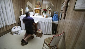 In this Aug. 9, 2019, photo Ron Sattler kneels and prays in front of the altar in Canton, Ohio. Late in the summer of 1939, crowds of strangers started showing up at Rhoda Wises house next to a city dump in Ohio after she let it be known that miracles were occurring in her room. Eight decades later, people still make pilgrimages to the wood frame bungalow at the edge of Canton, seeking their own miracles. (AP Photo/Tony Dejak)