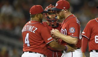 Washington Nationals relief pitcher Sean Doolittle, right, is pulled from the baseball game by manager Dave Martinez (4) during the ninth inning against the Milwaukee Brewers, Saturday, Aug. 17, 2019, in Washington. Catcher Kurt Suzuki is at rear. (AP Photo/Nick Wass)