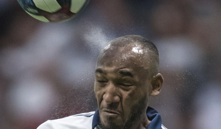 Vancouver Whitecaps' Derek Cornelius uses his head to clear the ball away from the goal area while defending against D.C. United during the first half of an MLS soccer match Saturday, Aug. 17, 2019, in Vancouver, British Columbia. (Darryl Dyck/The Canadian Press via AP)