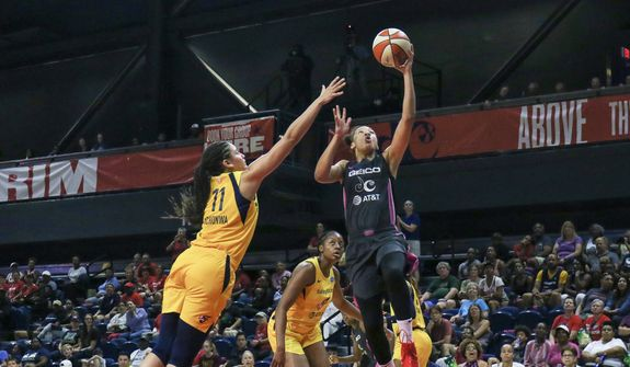 Washington Mystics forward Aerial Powers (left) splits the Indiana Fever defense on her way to the basket on Sunday. Powers finished with 19 points, including four 3-pointers, in a 107-68 victory. (Photograph by Arturo Holmes/Special to the Washington Times)