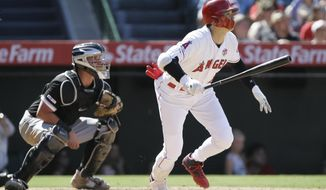Los Angeles Angels designated hitter Shohei Ohtani, right, watches his two-run home run with Chicago White Sox catcher James McCann, left, during the seventh inning of a baseball game in Anaheim, Calif., Sunday, Aug. 18, 2019. (AP Photo/Alex Gallardo)