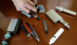 FILE — In this Tuesday, April 10, 2018 photo, a high school principal displays vaping devices that were confiscated from students at the school in Massachusetts. On Wednesday, Aug. 14, 2019, the Vapor Technology Association filed a lawsuit against the U.S. government to delay a review of electronic cigarettes. (AP Photo/Steven Senne)