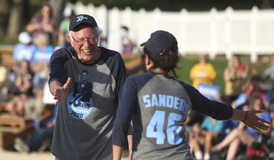 Democratic presidential candidate U.S. Sen. Bernie Sanders, I-Vt., cheers on his teammates before a softball game at the Field of Dreams in Dyersville, Iowa, Monday, Aug. 19, 2019. (Jessica Reilly/Telegraph Herald via AP)