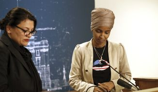 Rep. Ilhan Omar, D-Minn., right, and Rep. Rashida Tlaib, D-Mich., take a quiet moment as they talked about Israel's refusal to allow them to visit the country during a news conference Monday, Aug. 19, 2019, at the State Capitol in St. Paul, Minn. (AP Photo/Jim Mone)