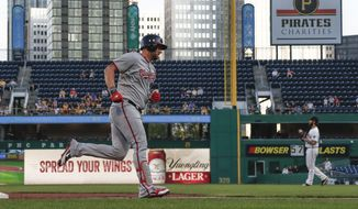 Washington Nationals' Matt Adams, left, rounds third after hitting a two-run home run off Pittsburgh Pirates starting pitcher Trevor Williams, right, in the first inning of a baseball game, Monday, Aug. 19, 2019, in Pittsburgh. (AP Photo/Keith Srakocic) **FILE**