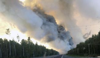 In this Sunday, Aug. 18, 2019 photo provided by the Alaska Division of Forestry, a smoke plume from the McKinley Fire is seen along the Parks Highway near Willow, Alaska. The main highway in Alaska that connects Anchorage and Fairbanks has reopened on a limited basis. A wildfire north of Willow jumped the Parks Highway on Sunday night, prompting a closure for a 9-mile stretch. The state Division of Forestry says one lane of traffic reopened at 8 a.m. Monday. (Maureen Clark/Alaska Division of Forestry via AP)