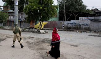 A Kashmiri woman walks past an Indian paramilitary soldier who prepares to block a road with barbed wires during security lockdown in Srinagar, Indian controlled Kashmir, Sunday, Aug. 18, 2019. (AP Photo/ Dar Yasin)