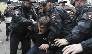 Police detain an activist during a protest in the center of Moscow, Russia, Saturday, Aug. 17, 2019. People rallied Saturday against the exclusion of some city council candidates from Moscow's upcoming election. (AP Photo)