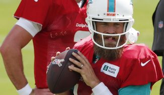 Miami Dolphins quarterback Ryan Fitzpatrick, foreground, runs a drill as quarterback Josh Rosen looks on during practice at the NFL football team's training camp, Monday, Aug. 19, 2019, in Davie, Fla. Fitzpatrick is expected to start the Miami Dolphins' exhibition game this week, which suggests he's still the front-runner in his battle with Rosen for the starting job. (AP Photo/Wilfredo Lee)