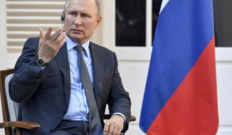 Russian President Vladimir Putin gestures at the fort of Bregancon in Bormes-les-Mimosas, southern France, Monday Aug. 19, 2019. French President Emmanuel Macron and Russian President Vladimir Putin are meeting to discuss the world's major crises, including Ukraine, Iran and Syria, and try to improve Moscow's relations with the European Union. (Gerard Julien, Pool via AP)