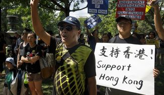"""People gather in Lafayette Square in front of the White House in Washington, Sunday, Aug. 18, 2019, in solidarity with the """"Stand With Hong Kong, Power to the People Rally"""" in Hong Kong. (AP Photo/Carolyn Kaster)"""