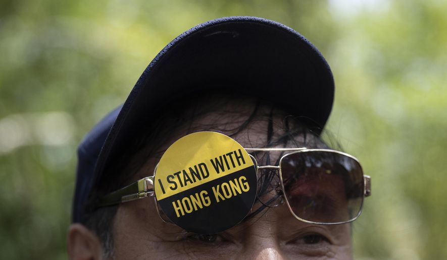 """A man with a sticker that reads """"I Stand With Hong Kong"""" on his glasses gathered with others in Lafayette Square in front of the White House in Washington, Sunday, Aug. 18, 2019, in solidarity with the """"Stand With Hong Kong, Power to the People Rally"""" in Hong Kong. (AP Photo/Carolyn Kaster)"""