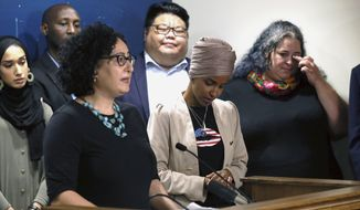 Rep. Ilhan Omar, D-Minn., center, listens as Lana Barkawi, left, talks about Israel travel restrictions she has faced during a news conference Monday, Aug. 19, 2019 at the State Capitol in St. Paul, Minn., held by Omar and Rep. Rashida Tlaib, D-Mich., who talked about Israel's refusal to allow them to visit the country. Barkawi is a Palestinian-American. Others who have faced travel restrictions are shown during the news conference. (AP Photo/Jim Mone)