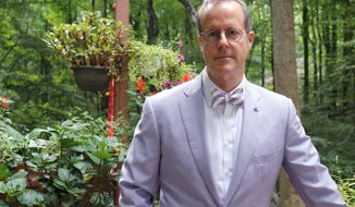In this Thursday, Aug. 1, 2019 file photo, Bruce Fleming, a tenured civilian English professor who has been a longtime critic of the Naval Academy, stands on the deck of his home after an interview in Davidsonville, Md. Fleming, with tenure at the U.S. Naval Academy who was fired by the school last year has returned to campus, Monday, Aug. 19, 2019. (AP Photo/Brian Witte)