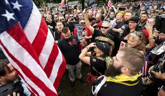 """Members of the Proud Boys and other right-wing demonstrators plant a flag in Tom McCall Waterfront Park during an """"End Domestic Terrorism"""" rally in Portland, Ore., on Saturday, Aug. 17, 2019. (AP Photo/Noah Berger)"""