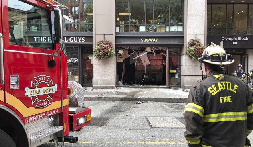 "In this Monday, Aug. 19, 2019, photo provided by the Seattle Fire Department, a firefighter looks on at the scene of where a dump truck crashed into a Subway restaurant in Seattle's historic Pioneer Square district, injuring five people. The Seattle Fire Department said four of the people had serious injuries and all were taken to a nearby hospital Monday morning. Seattle Police say the truck ""allegedly suffered a catastrophic mechanical failure,"" coming to rest completely inside the Subway, having shattered the entire front window of the store. (Seattle Fire Department via AP)"