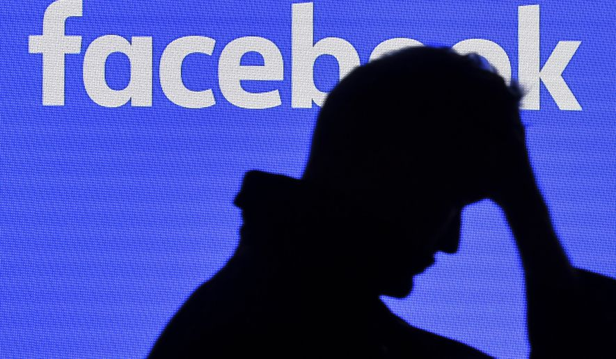 A man passes a facebook screen at the Gamescom in Cologne, Germany, Tuesday, Aug. 20, 2019. (AP Photo/Martin Meissner)
