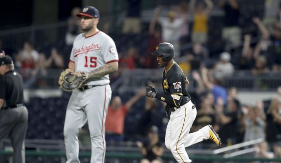 Pittsburgh Pirates' Starling Marte runs behind Washington Nationals first baseman Matt Adams (15) after hitting a two-run home run in the eighth inning of a baseball game, Tuesday, Aug. 20, 2019, in Pittsburgh. The Pirates won 4-1. (AP Photo/Keith Srakocic)