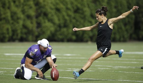 Baltimore Ravens' Sam Koch holds the ball for United States soccer player Carli Lloyd as she attempts to kick a field goal after the Philadelphia Eagles and the Baltimore Ravens held a joint NFL football practice in Philadelphia, Tuesday, Aug. 20, 2019. (AP Photo/Matt Rourke) ** FILE **