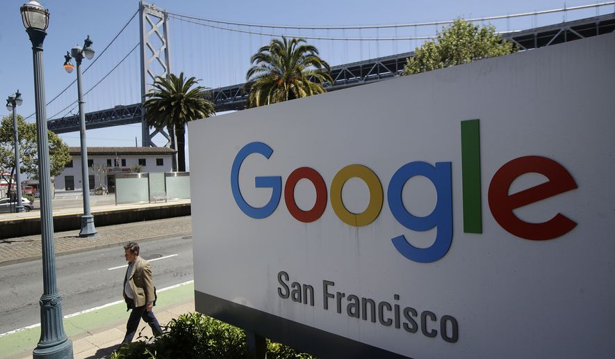 FILE - In this May 1, 2019, file photo a man walks past a Google sign outside with a span of the Bay Bridge at rear in San Francisco.  (AP Photo/Jeff Chiu, File)