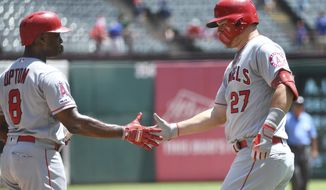 Los Angeles Angels' Mike Trout (27) is congratulated by Justin Upton (8) after hitting a two run home run off of Texas Rangers starting pitcher Joe Palumbo that scored David Fletcher during the first inning of the first baseball game of a doubleheader Tuesday, Aug. 20, 2019, in Arlington, Texas. (AP Photo/Jeffrey McWhorter)