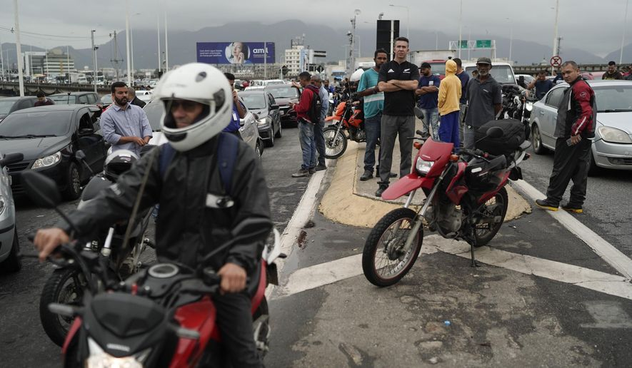 People wait at a blocked access of the bridge connecting the city of Niteroi to Rio de Janeiro , Brazil, Tuesday, Aug. 20, 2019 during a hostage standoff. An armed man holding dozens of people hostage on a public bus and threatening to set the vehicle on fire was seized by police after a four-hour long standoff, Brazilian police said.  (AP Photo/Leo Correa)