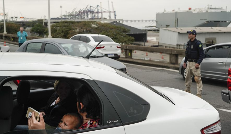 A woman sits in a car with a baby as they wait on a blocked access as a Federal Highway Police officer stands next at the busy bridge connecting the city of Niteroi to Rio de Janeiro, Brazil, Tuesday, Aug. 20, 2019, during a hostage standoff. An armed man holding dozens of people hostage on a public bus and threatening to set the vehicle on fire was seized by police after a four-hour long standoff, Brazilian police said.  (AP Photo/Leo Correa)