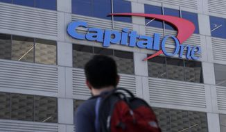 FILE - In this July 16, 2019, file photo, a man walks across the street from a Capital One location in San Francisco. Federal prosecutors say Paige Thompson, the woman accused of hacking Capital One and at least 30 other organizations, is a threat to herself and society, a flight risk and should be kept locked up until her trial. (AP Photo/Jeff Chiu, File)