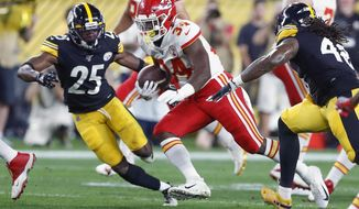 Kansas City Chiefs running back Carlos Hyde (34) runs between Pittsburgh Steelers outside linebacker Bud Dupree (48) and cornerback Artie Burns (25) in the first half of a preseason NFL football game, Saturday, Aug. 17, 2019, in Pittsburgh. (AP Photo/Don Wright)