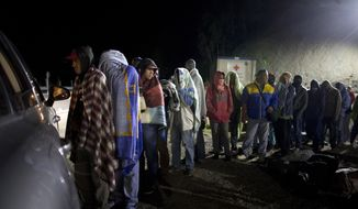 FILE - In this Aug. 31, 2018 file photo, Venezuelan migrants line up for free bread and coffee, donated by a Colombian family from their car, at a gas station in Pamplona, Colombia. A United Nations special envoy warned on Tuesday, Aug. 20, 2019, that the international community is falling short in helping nations like Colombia respond to the massive exodus of Venezuelans. (AP Photo/Ariana Cubillos, File)