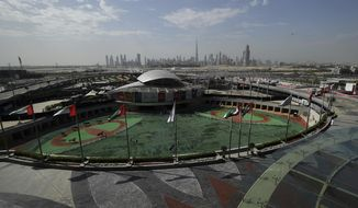 """FILE - In this March 30, 2019 file photo, horses warm up in the saddling enclosure ahead of Dubai Kahayla Classic at the Meydan Racecourse in Dubai, United Arab Emirates. Dubai said Tuesday, Aug. 20, 2019, that it had set up a special committee to """"resolve multiple disputes"""" involving the government-owned developer Meydan as it faces a series of lawsuits amid an economic slowdown gripping the city-state. (AP/Martin Dokoupil, File)"""