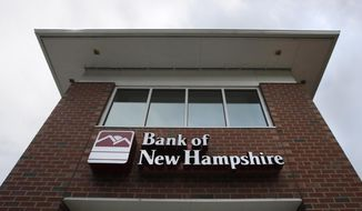 Clouds pass over the Bank of New Hampshire branch in Manchester, N.H., Monday, Aug. 19, 2019. An economic empowerment program for domestic violence survivors in New Hampshire is boosting their bank accounts and their self-esteem. The partnership with Bank of New Hampshire allows participants to open savings accounts where their savings are matched dollar for dollar. (AP Photo/Charles Krupa)