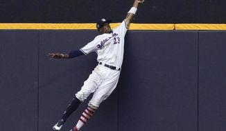FILE - In this July 4, 2018, file photo, Milwaukee Brewers' Keon Broxton makes a leaping catch at the wall on a ball hit by Minnesota Twins' Brian Dozier during the ninth inning of a baseball game in Milwaukee. Everyone has seen an outfielder receive a tip of the cap or a jubilant fist bump from a pitcher after a home run robbery. This is a story about what happens after they leave the field. (AP Photo/Morry Gash, File)