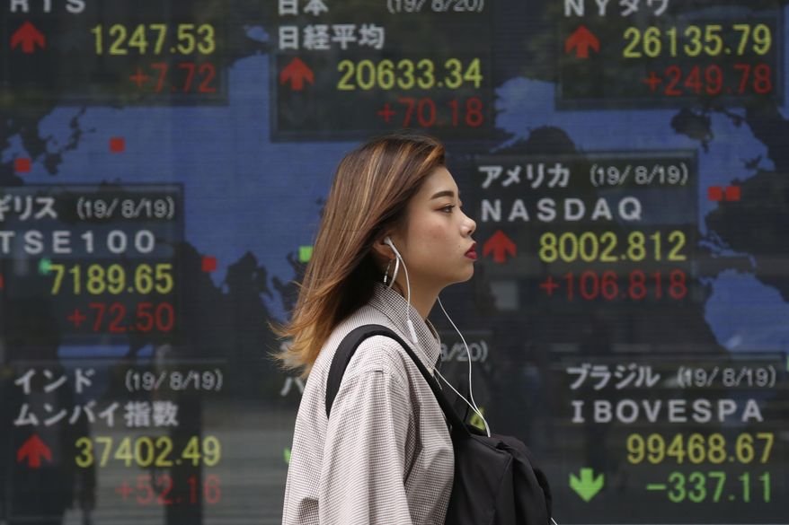 A woman walks by an electronic stock board of a securities firm in Tokyo, Tuesday, Aug. 20, 2019. Asian shares were mostly higher Tuesday after Wall Street rallied on the U.S. decision to give Chinese telecom giant Huawei another 90 days to buy equipment from American suppliers. (AP Photo/Koji Sasahara)