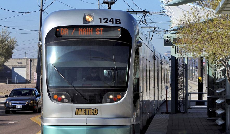 FILE - In this Jan. 16, 2016 file photo, a Metro Light Rail train stops for passengers in Phoenix. Campaigning over the future of mass rail transit in this Southwestern desert metropolis is heating up over next week's election asking voters whether they want to halt any expansion of the light rail system in the nation's fifth largest city. (AP Photo/Paul Davenport, File)