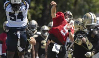New Orleans Saints quarterback Drew Brees, center, throws a pass over Los Angeles Chargers defensive end Melvin Ingram, left, during a joint NFL football practice in Costa Mesa, Calif., Friday, Aug. 16, 2019. (AP Photo/Kyusung Gong)