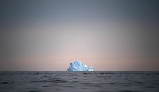 In this Aug. 15, 2019, photo, a large Iceberg floats away as the sun sets near Kulusuk, Greenland. Greenland is where Earth's refrigerator door is left open, where glaciers dwindle and seas begin to rise. Scientists are hard at work there, trying to understand the alarmingly rapid melting of the ice. For Greenland is where the planet's future is being written. (AP Photo/Felipe Dana)