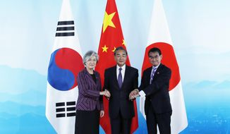 Chinese Foreign Minister Wang Yi, center, holds hands of his South Korean counterpart Kang Kyung-wha, left, and Japanese counterpart Taro Kono ahead of their trilateral meeting at Gubei Town in Beijing Wednesday Aug. 21, 2019. (Wu Hong/Pool Photo via AP)