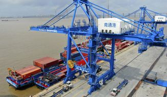 """In this July 18, 2019, file photo, shipping containers are loaded onto a cargo ship at a port in Nantong in eastern China's Jiangsu province. Beijing appealed to Washington on Wednesday, Aug. 21, to """"meet China halfway"""" and end a tariff war after President Donald Trump said Americans might need to endure economic pain to achieve longer-term benefits. (Chinatopix via AP)"""