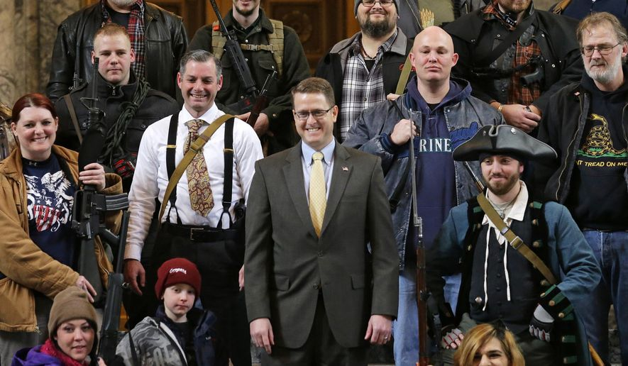 FILE - In this Jan. 15, 2015, file photo, Washington state Rep. Matt Shea, R-Spokane Valley, center, poses for a group photo with gun owners inside the Capitol in Olympia, Wash., following a gun-rights rally. The mayor and police chief of Spokane, Wash., are the latest to demand that the conservative state legislator resign from office after leaked emails revealed he sought to conduct surveillance on local progressive leaders. Mayor David Condon and Police Chief Craig Meidl on Tuesday, Aug. 20, 2019 denounced Shea, who wants to create a 51st state based on Christian principles.(AP Photo/Ted S. Warren, File)